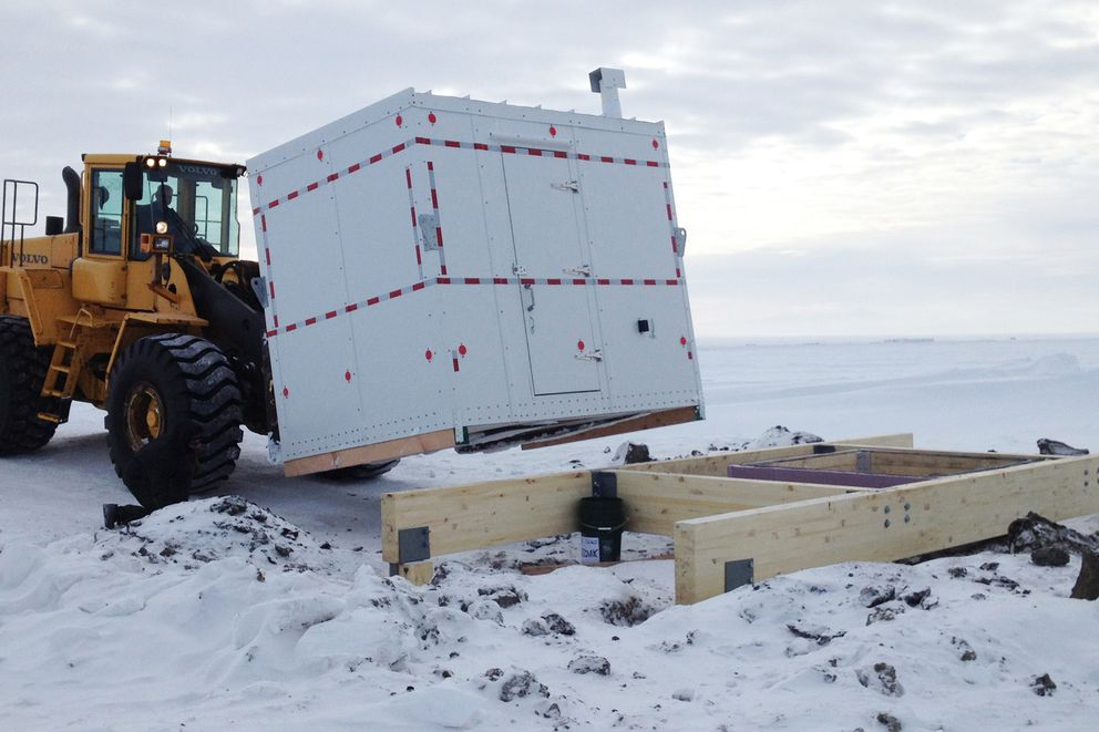 This undated photo in Kaktovik, Alaska, shows installation of a shelter covering the entrance to a new community ice cellar, a type of underground food cache dug into the permafrost to provide natural refrigeration used for generations in far-north communities. Naturally cooled underground ice cellars, used in Alaska Native communities for generations, are becoming increasingly unreliable as a warming climate and other factors touch multiple facets of life in the far north. (Marnie Isaacs/Kaktovik Community Foundation via AP)
