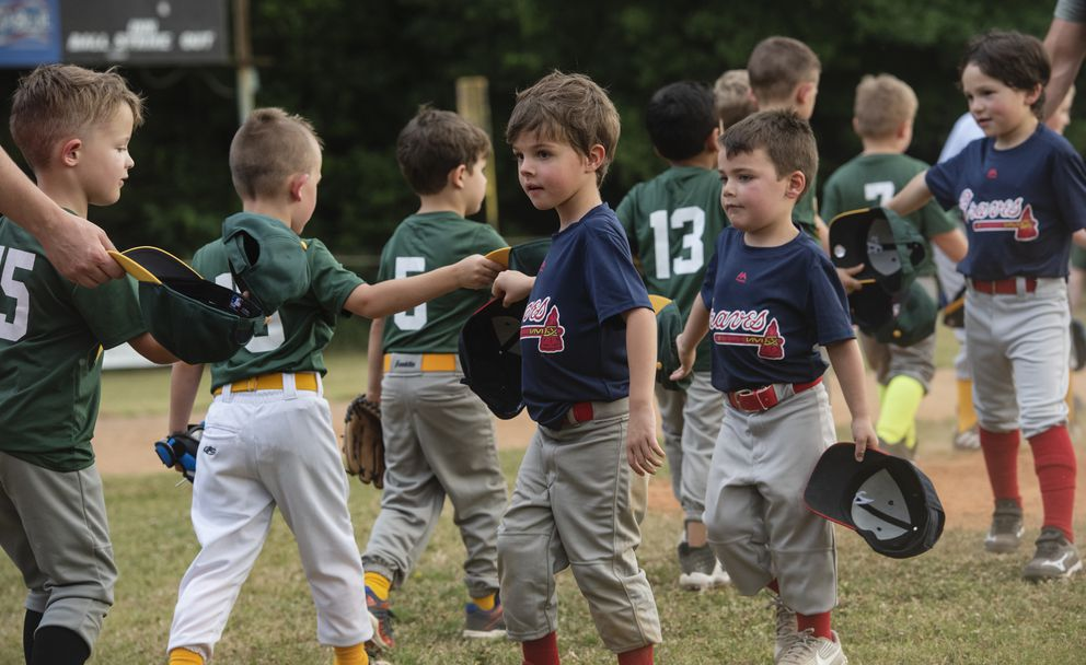 Members of the Braves T-ball team tap their hats with members of the Athletics team instead of giving high-fives to maintain less physical contact at the end of a baseball game Monday, June 15, 2020, at Golden Road Park in Tyler, Texas. The Rose Capital East Little League teams held their first games Monday, after a delay in the season due to COVID-19. (Sarah A. Miller/Tyler Morning Telegraph via AP)