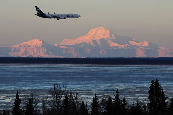 An Alaska Airlines passenger jet lands at the airport on Thursday, Nov. 30, 2017, as warm sunlight from the setting sun illuminates Mt. Hunter and Denali and mountains in the Alaska Range which are distorted by the atmospheric phenomenon known as Fata Morgana, an optical distortion of the horizon due to temperature inversions. (Bill Roth / ADN)