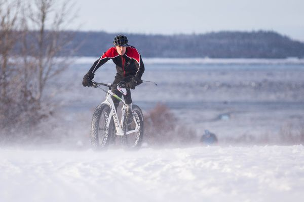Joe Reser is battered by blowing wind and snow at the finish of the Frosty Bottom bike race at Kincaid Park on Saturday, Jan. 14, 2017. (Loren Holmes / Alaska Dispatch News)