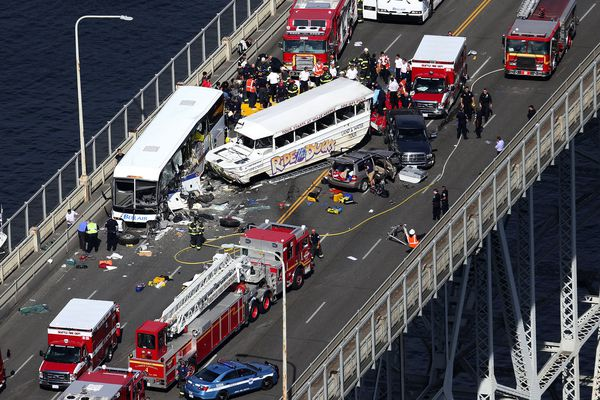 Emergency personnel work at the scene of a fatal collision involving a charter bus and a Ride the Ducks amphibious tour bus on the Aurora Bridge in Seattle on Thursday.