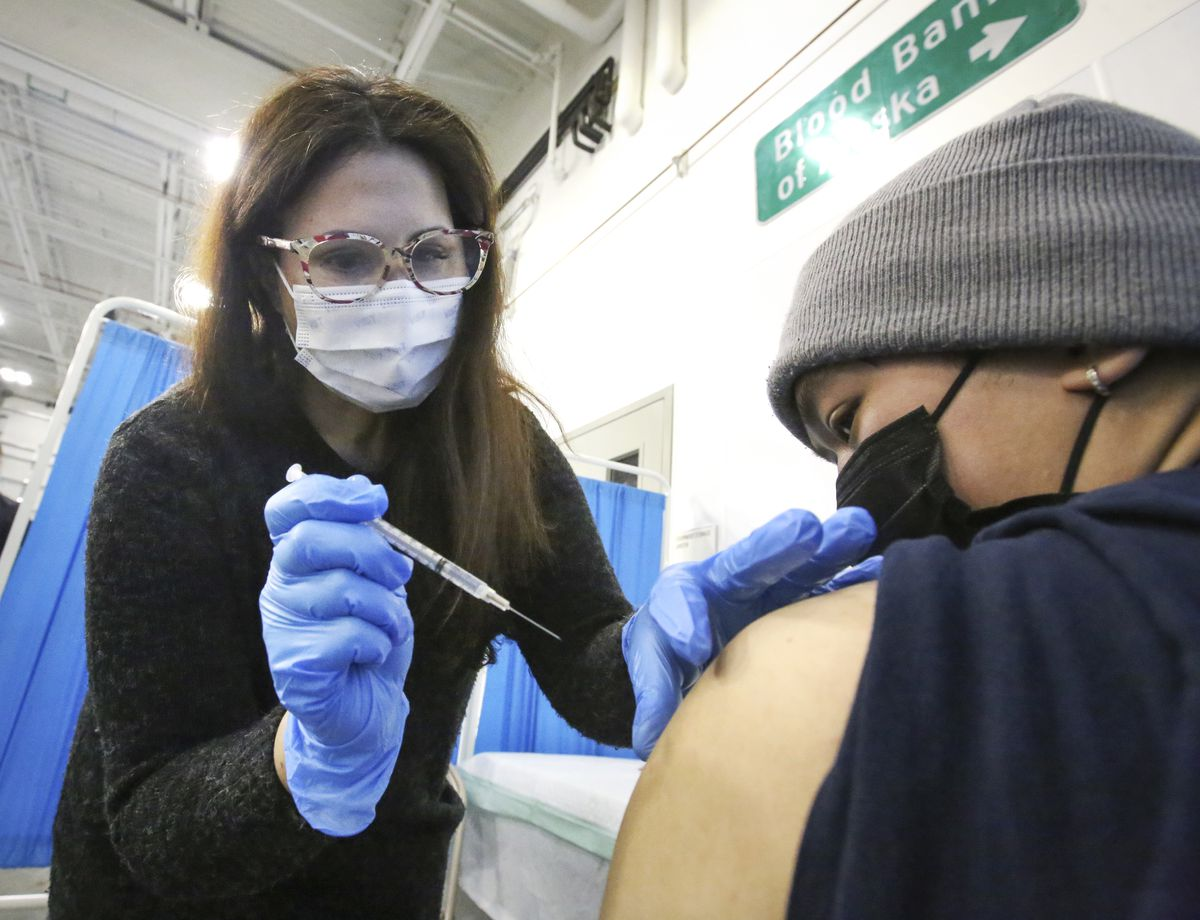 Barbara Brena administers the first dose of a Pfizer-BioNTech COVID-19 vaccine to Lesther Sudaria, 23, at the Blood Bank of Alaska in Anchorage on Wednesday. (Emily Mesner / ADN)