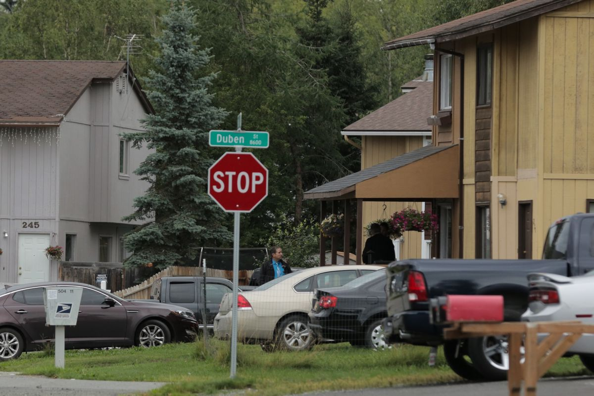 Police canvass residents along Bolin Street the morning after Treyveonkindell Thompson was discovered dead on July 29, 2016. (Loren Holmes / Alaska Dispatch News)