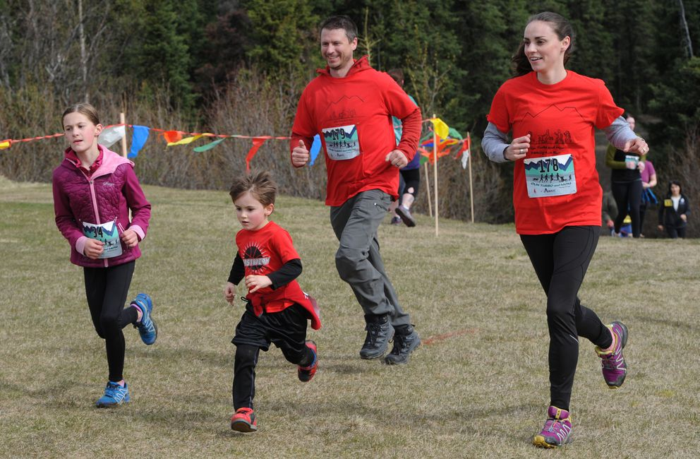 Olin 'Turbo ' Ahonen, 4, sprints to the finish with his parents Adam and Mary Ahonen close behind during the 2K family fun run at Service High School on Mother's Day, Sunday, May 12, 2019. (Bill Roth / ADN)