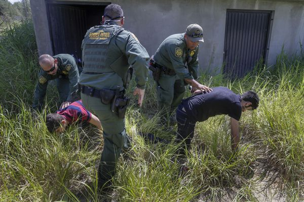 Border Patrol agents capture young immigrants after a chase through neighborhood streets in Roma, Texas, on August 3, 2018. (Tribune News Service)
