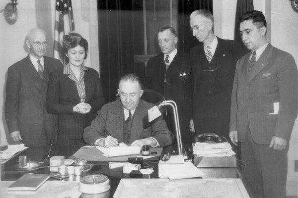 Alaska Territorial Gov. Ernest Gruening signs the territory's anti-discrimination bill that outlawed segregation of Alaska Natives on Feb. 16, 1945. Joining him , from left, were Nome Sen. O.D. Cochran, rights activist Elizabeth Peratrovich, representing the Alaska Native Sisterhood, Rep. Edward Anderson of Nome, Sen. N.R. Walker of Ketchikan and Roy Peratrovich, Elizabeth's husband who represented the Alaska Native Brotherhood. (Anchorage Museum of History and Art)
