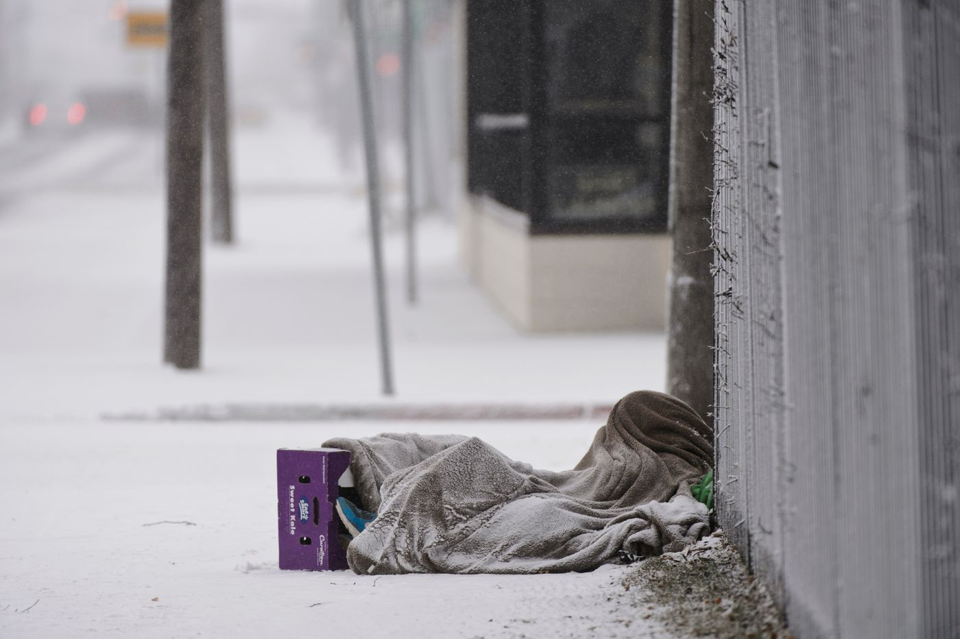 A person lies under a blanket along 5th Avenue as snow falls on November 6, 2020. (Marc Lester / ADN)