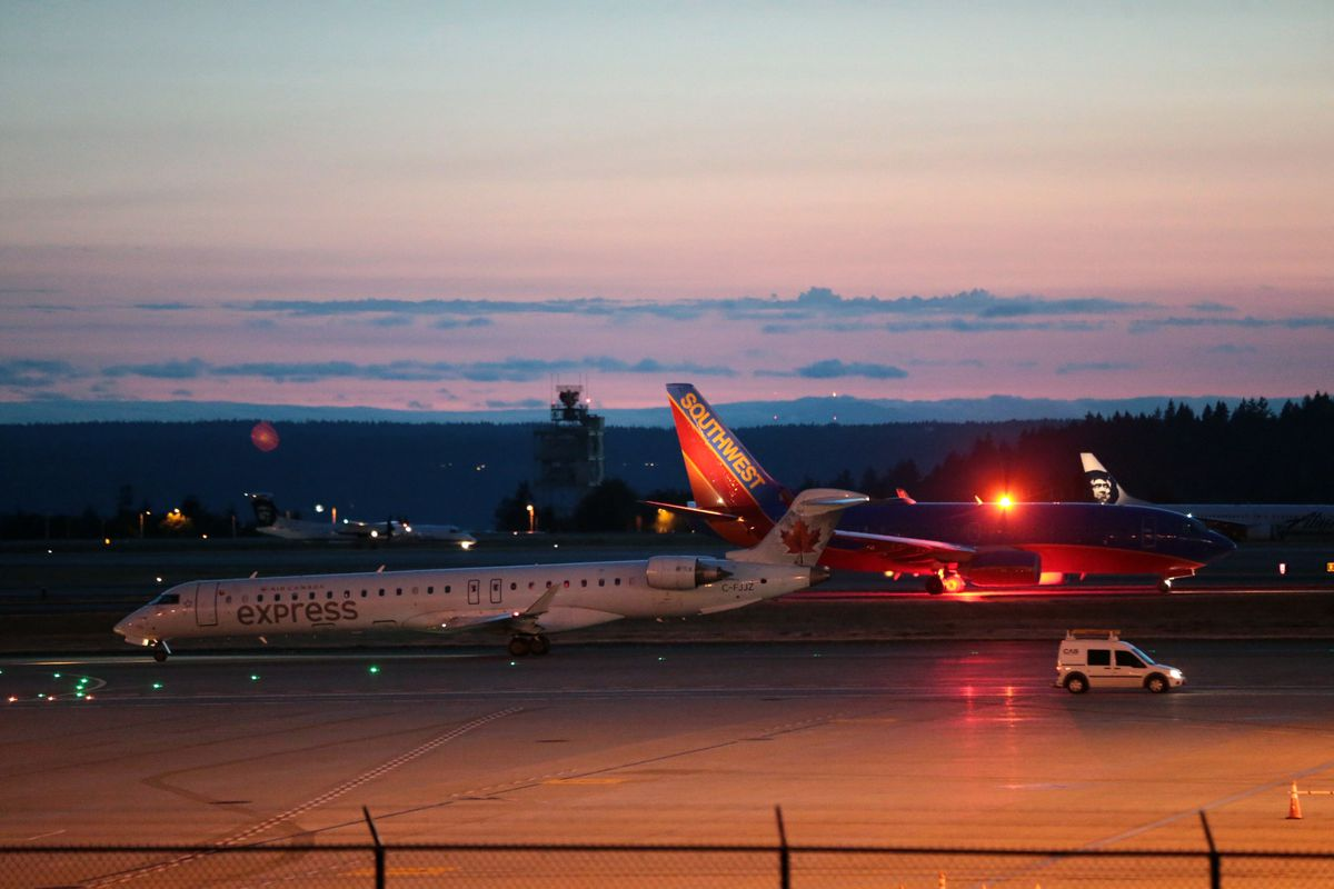 Planes sit on the tarmac at Sea-Tac International Airport after service was halted after an Alaska Airlines plane was stolen Friday, Aug. 10, 2018, in Wash. (Bettina Hansen /The Seattle Times via AP)