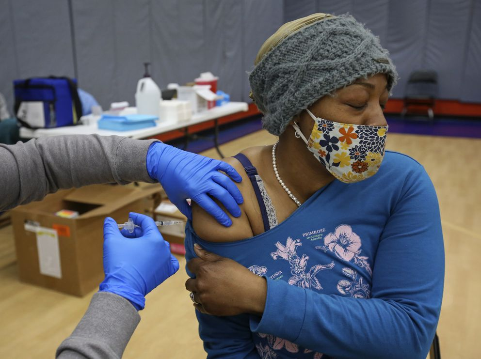 Ayanna Green closes her eyes as Kadie Hansen administers a dose of the COVID-19 vaccine. (Emily Mesner / ADN)