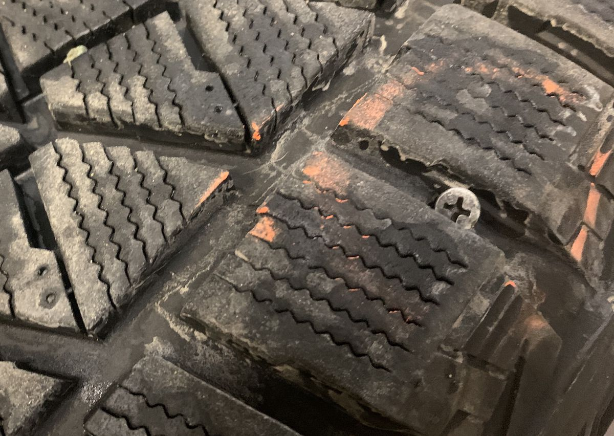 A tire with a drywall screw embedded in its tread sits inside the Alaska Tire Service lobby in Eagle River on Thursday, Jan. 23, 2020. Thousands of the screws spilled onto the road Thursday, puncturing the tires of numerous motorists on Eagle River Loop Road. (Matt Tunseth / ADN)