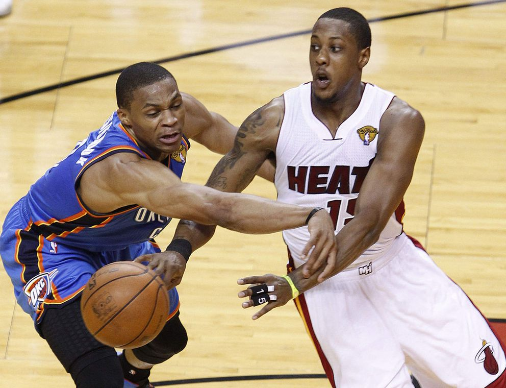 Miami Heat point guard Mario Chalmers, right, passes as Oklahoma City Thunder point guard Russell Westbrook defends during the first half at Game 5 of the NBA finals basketball series, Thursday, June 21, 2012, in Miami. (AP Photo/Wilfredo Lee)