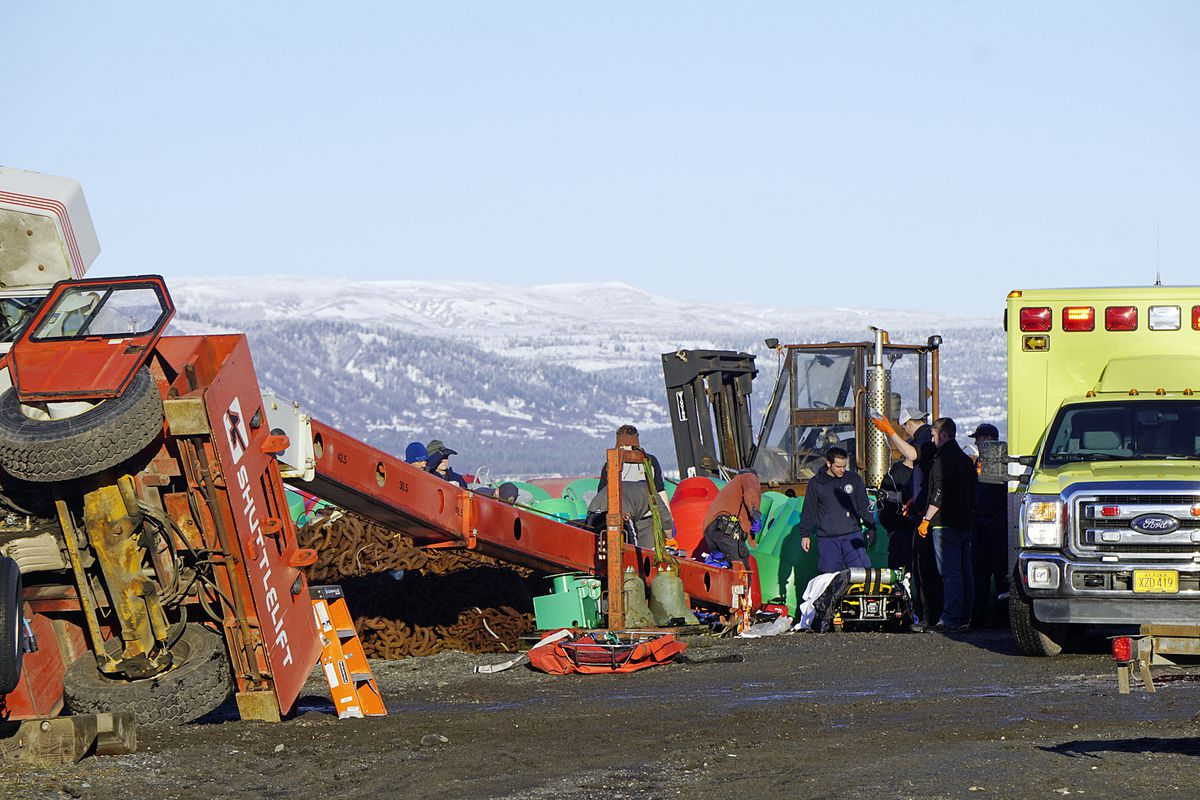 This Thursday, Jan. 31, 2019 photo shows Homer Volunteer Fire Department emergency medical technicians treating a person injured when a crane tipped over in the buoy yard of the U.S. Coast Guard Cutter Hickory at the Pioneer Dock on the Homer Spit in Homer, Alaska. (Michael Armstrong/Homer News via AP)