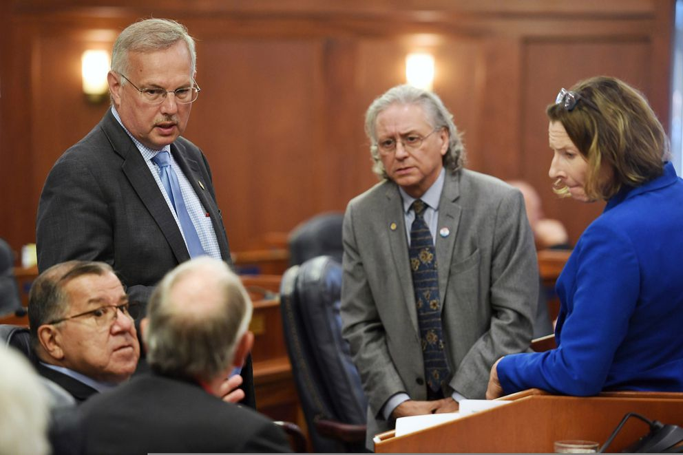 Leadership of the Alaska House and Senate confer Wednesday, July 10, 2019, at the state Capitol in Juneau, Alaska, where lawmakers failed to override Gov. Mike Dunleavy's budget vetoes. About a third of the lawmakers were absent from the Juneau session, choosing to meet in Wasilla instead. Standing are House Speaker Bryce Edgmon, from left, Senate Minority Leader Tom Begich and Senate President Cathy Giessel. Seated are Senate Majority Leader Lyman Hoffman, left, and House Majority Leader Steve Thompson, with his back to the camera. (Michael Penn/The Juneau Empire via AP)