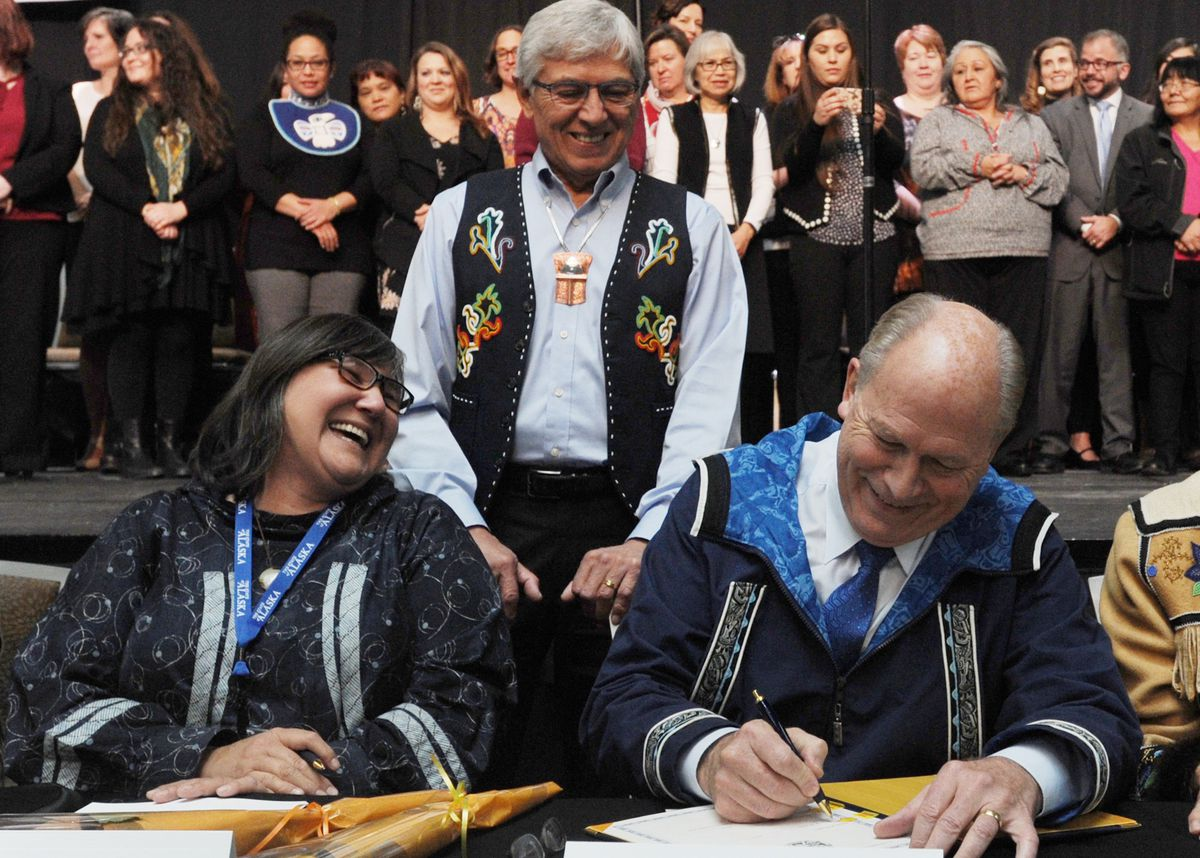 Department of Health and Social Services Commissioner Valerie Davidson, left, and Gov. Bill Walker , right, sign Alaska Tribal Child Welfare Compact on the first day of AFN at the Dena'ina Center in Anchorage on Thursday, Oct. 19, 2017. Lt. Gov. Byron Mallott, center, watches the historic signing with tribal leaders. (Bill Roth / ADN)