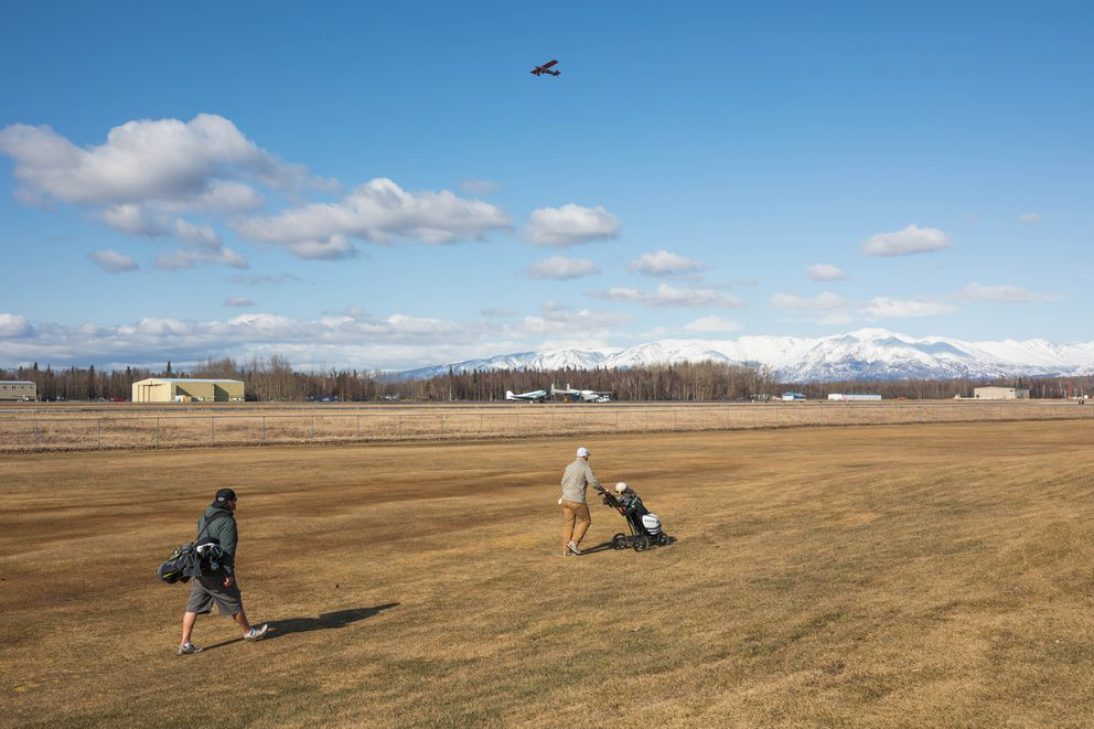 Wes Masters, left, and Derek O'Neill walk down hole number 3 at the Palmer Golf Course on Friday. The course wraps around the nearby Warren 'Bud ' Woods Palmer Municipal Airport. (Loren Holmes / ADN)