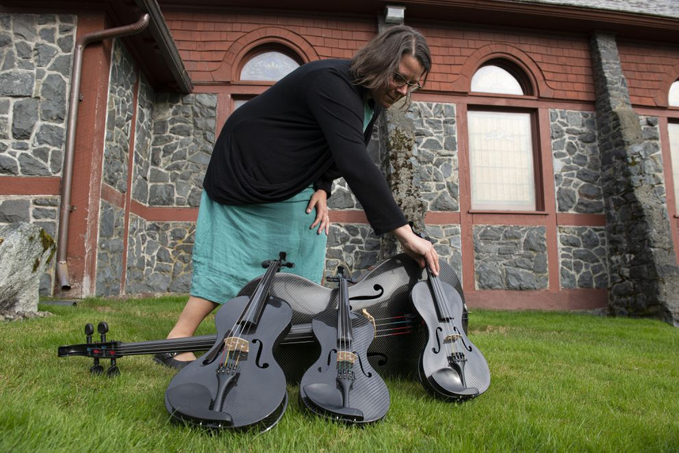 Sitka Summer Music Festival executive drector Kayla Boettcher stands with the festival's carbon fiber instruments at St. Peter's-by-the-Sea Episcopal Church on September 5, 2019, in Sitka, Alaska. (Photo by James Poulson)