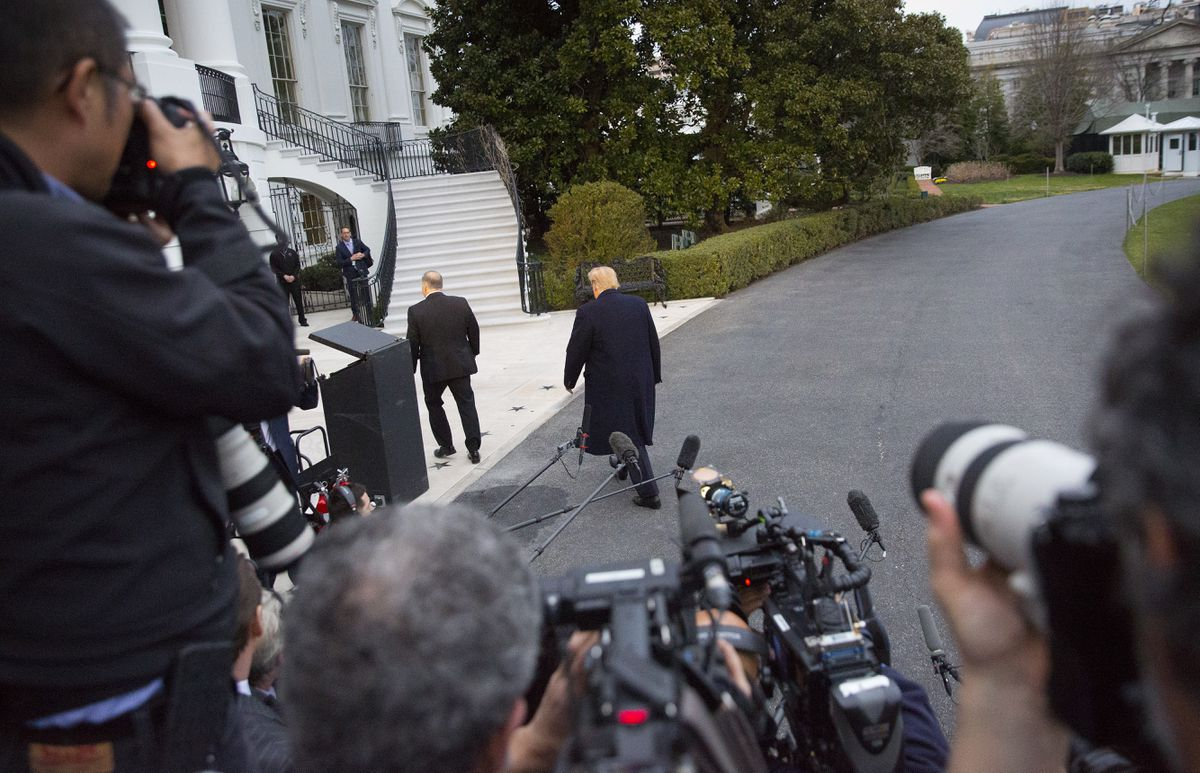 President Donald Trump, center, walks away after speaking to the media following his arrival on Marine One helicopter on the South Lawn of the White House, Sunday, March 24, 2019, in Washington. The Justice Department said Sunday that special counsel Robert Mueller's investigation did not find evidence that President Donald Trump's campaign