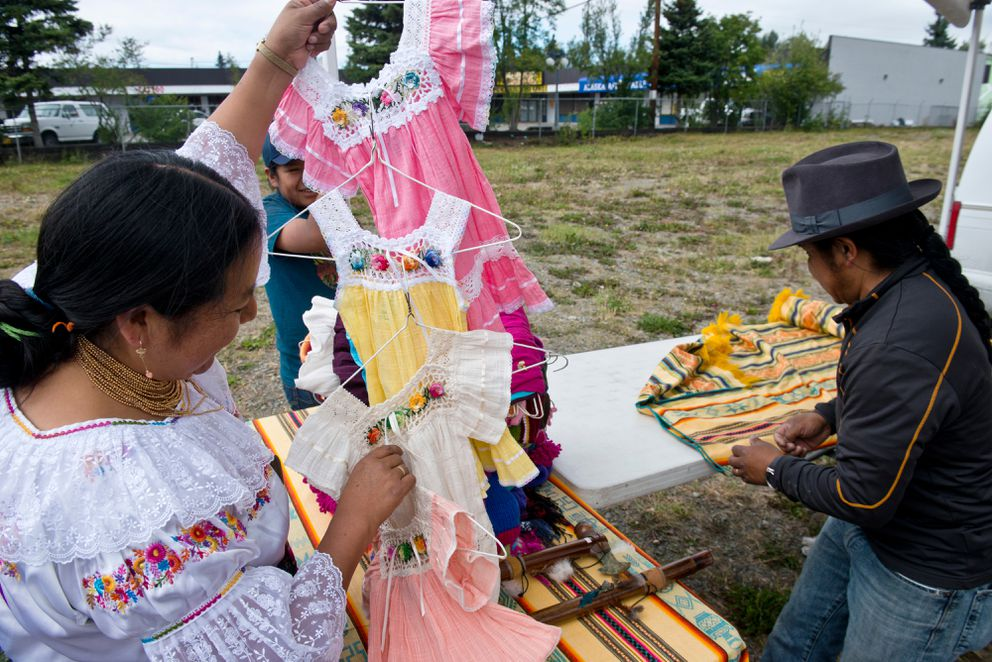 Aida Ramos, left, displays clothing at her Mountain View Farmers Market stand on Thursday, July 21, 2016. She makes Ecuadorian clothing from alpaca wool and other materials. (Marc Lester / Alaska Dispatch News)