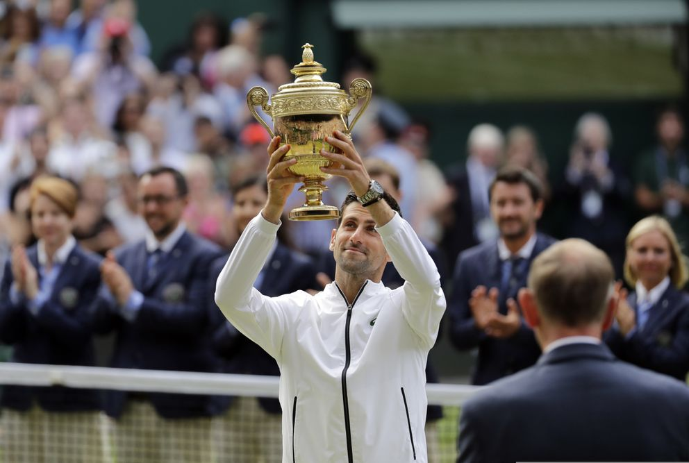 Serbia's Novak Djokovic lifts his trophy after defeating Switzerland's Roger Federer during the men's singles final match of the Wimbledon Tennis Championships in London, Sunday, July 14, 2019. (AP Photo/Ben Curtis)