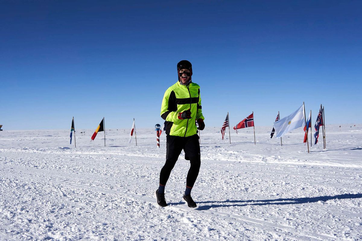 Craig Updegrove of Bethel runs past the flags that mark the ceremonial South Pole during his 90-kilometer run in January. (Courtesy Geoffrey Chen)