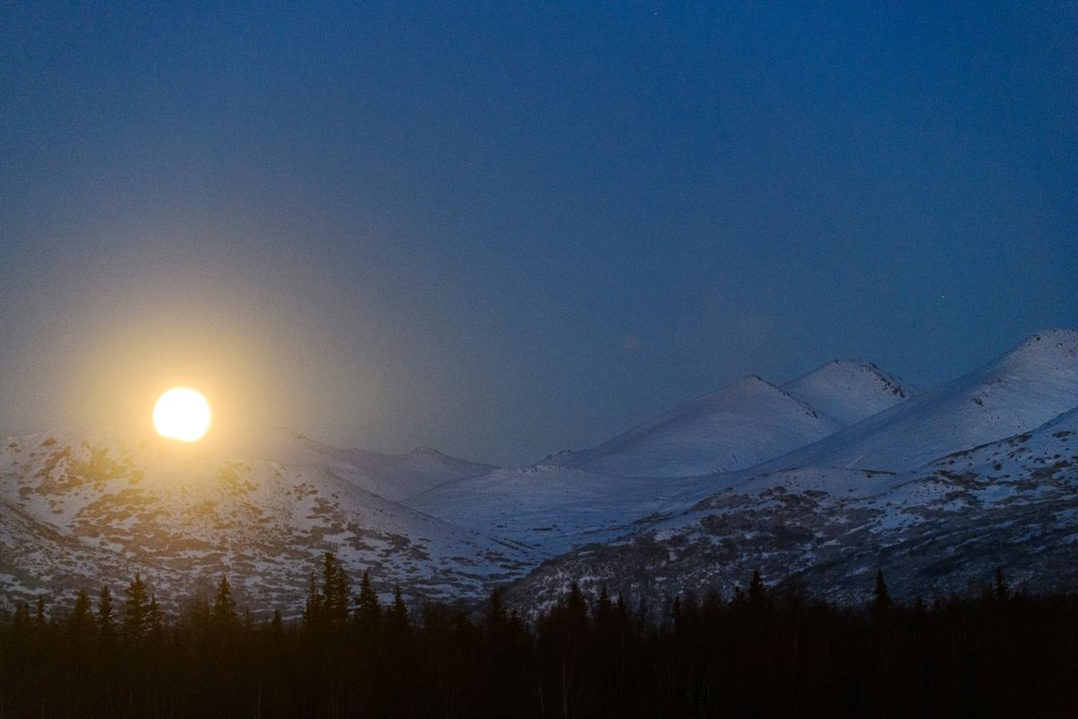 The full moon rises over the Chugach Mountains in this view from Midtown Anchorage on October 30, 2020. It was the second full moon of the month, also known as a blue moon. (Marc Lester / ADN)