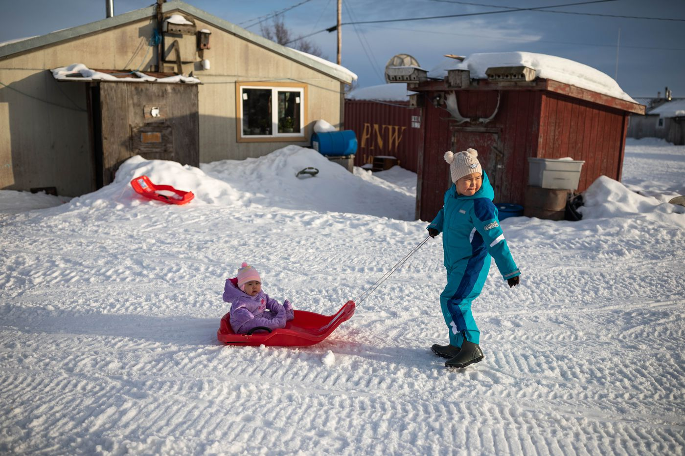 Isabella Takumjenak, 7, pulls her sister Rosetta Kozevmikoff, 10 months, on a sled outside their family home on March 7, 2019 in Russian Mission. (Loren Holmes / ADN)