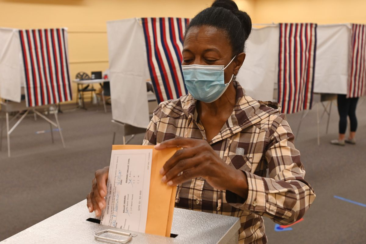 Paulette Shaw places her primary election ballot in a ballot box while voting early at the Midtown Mall early on Monday, August 17, 2020. (Bill Roth / ADN)