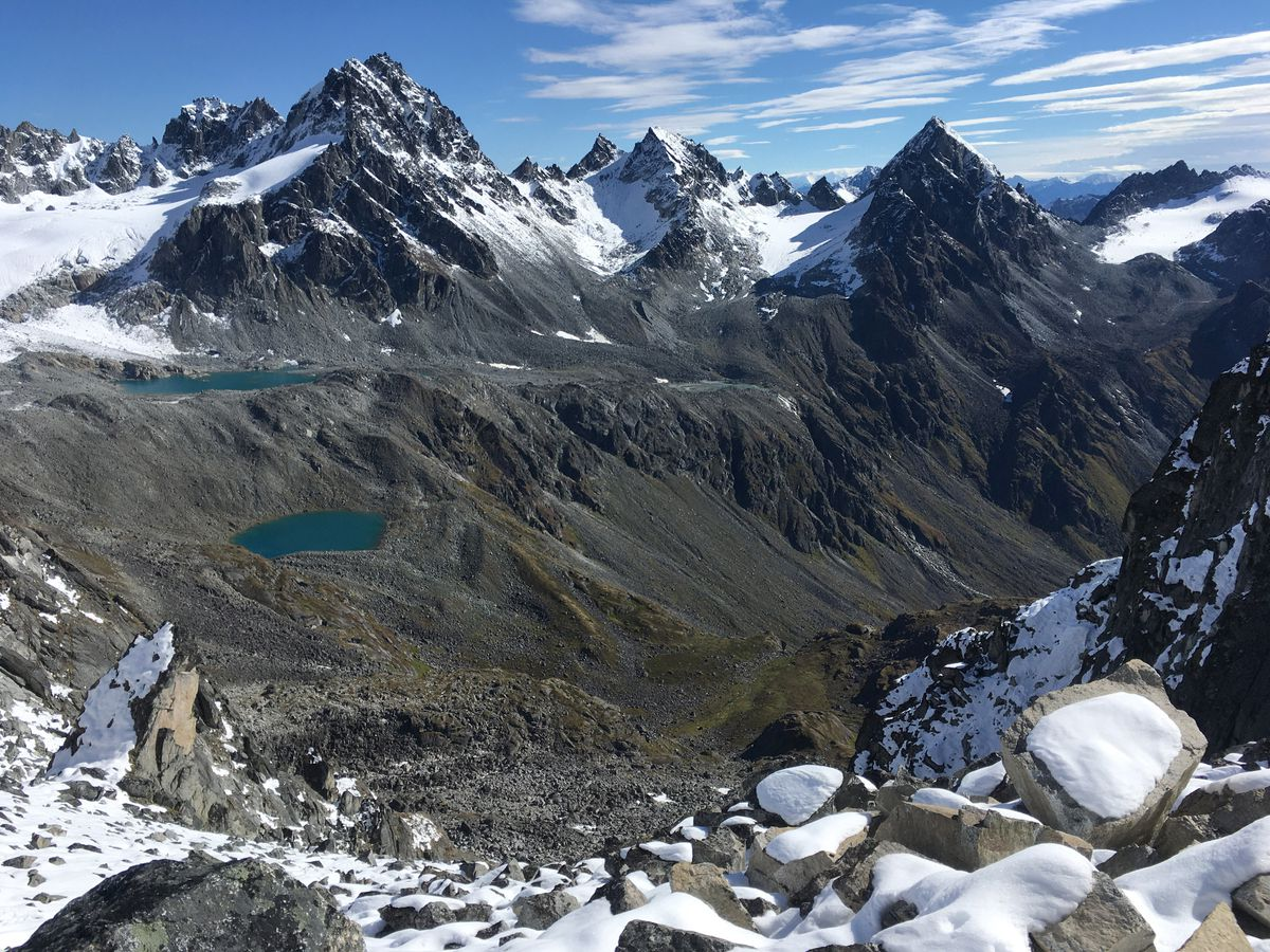 View from the top of Backdoor Gap of the Bomber Traverse in the Talkeetna Mountains. For scale, squint at the lower right-hand corner and you will see the tiny green roof of the Mint Hut. (Photo by Alli Harvey)