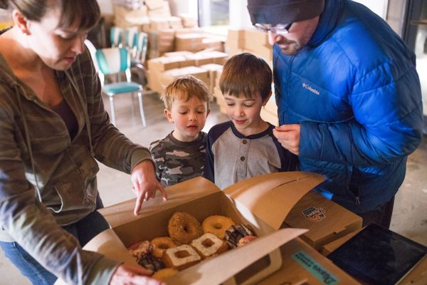 Dipper Donuts co-owner Laura Cameron shows Trevor Snyder and his sons Emmett, 5, and Graham, 7, the day's doughnut selection on Wednesday, Nov. 22, 2017. The Spenard coffee and doughnut shop is open Tuesdays through Fridays for boxes of donuts from 6 a.m. until the goods sell out. (Loren Holmes / ADN)