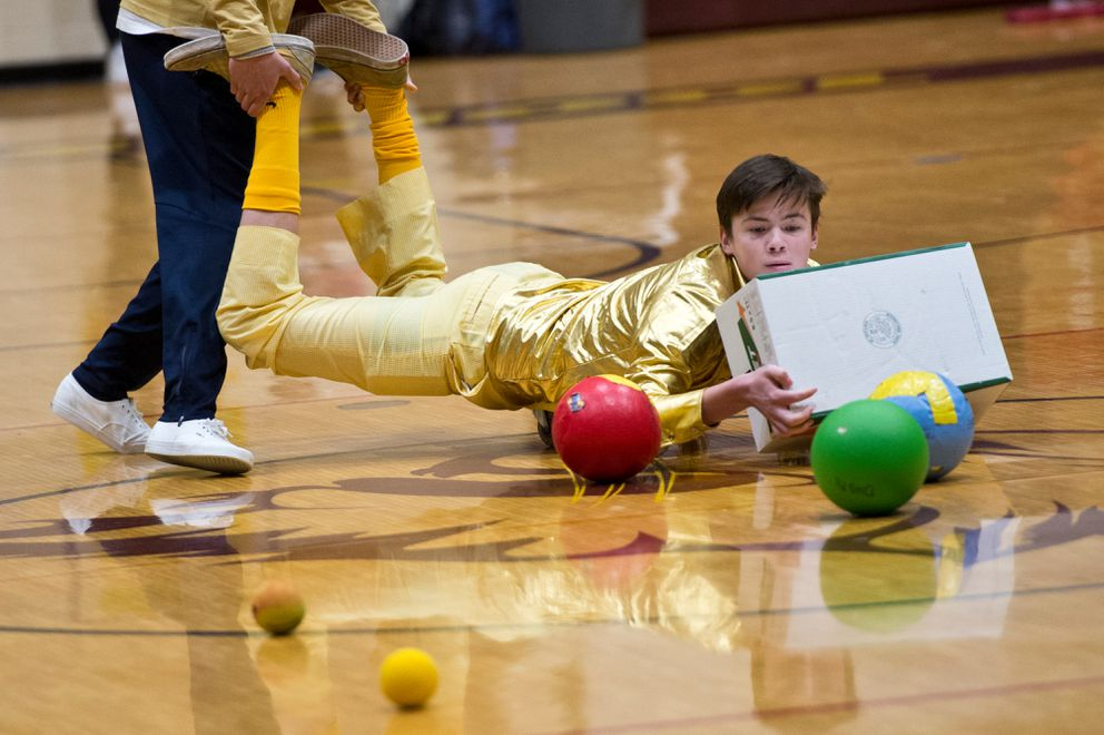 Junior Will Fagerstrom gathers rubber balls in the Hungry Hippo game with help from a teammate. (Marc Lester / Anchorage Daily News)