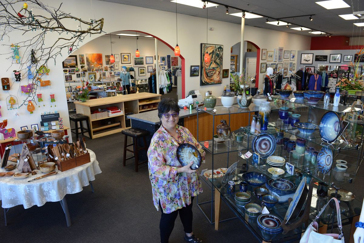 Owner Jacqui Ertischek holds a plate by Bill Campbell at the 2 Friends Gallery. The gallery that sells consignment artwork has recently expanded. (Bob Hallinen / Alaska Dispatch News)