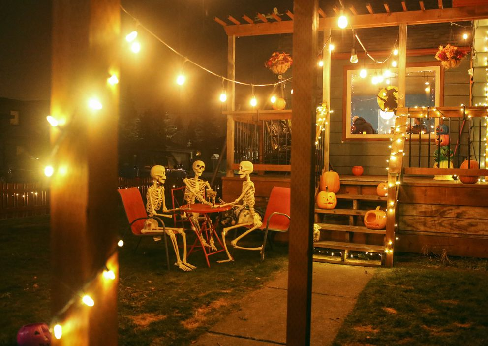 Skeletons sit around a table as part of Halloween decorations outside a South Addition home on H Street in Anchorage on Oct. 28, 2020. (Emily Mesner / ADN)
