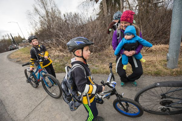 Olympian Holly Brooks, carrying her 8-month-old twins Brooks and Ruby Joy Whitney, greets fourth-grader Zachary Kenny, left, and first-grader Chase Kenny as they bike to school at Huffman Elementary Wednesday, May 9, 2018. (Loren Holmes / ADN)