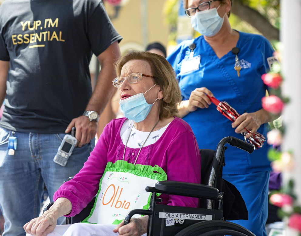 In this Saturday, May 9, 2020 photo, Olbia Ferrer looks at her family as they wave to her from their vehicle during a Mother's Day drive-by caravan to honor the mothers living at The Palace Renaissance & Royale, an assisted living facility in Kendall, Fla. It has been a year since Ferrer moved to the The Palace Renaissance memory facility due to her Alzheimers, and two months since she last saw her family after the coronavirus pandemic started. (Daniel A. Varela/Miami Herald via AP)