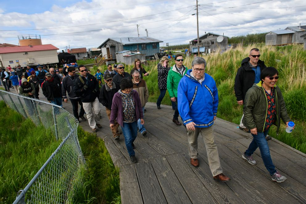 In blue, U.S. Attorney General William Barr walks the Napaskiak boardwalk with tribal administrator Sharon Williams, right, and others on Friday, May 31, 2019. Barr visited Bethel and Napaskiak to learn about law enforcement and public safety challenges in the region. (Marc Lester / ADN)