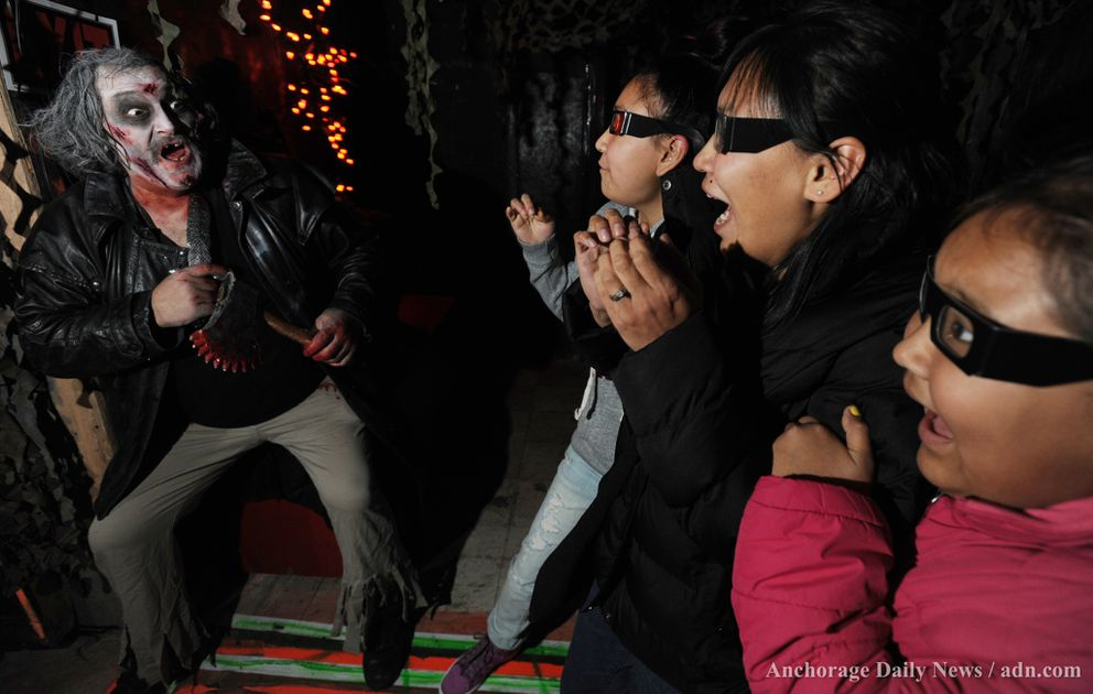 Dave Rodrigues the 'Grave Digger ' scares Allison Nashoanak, 17, her mother Carol Nashoanak, and Kailey Nashoanak, 10, as they walk through the dark halls wearing 3-D glasses in the Fright Nite Haunted House at the Northway Mall on Sunday, Oct. 27, 2013. Fright Nite opens at 6 p.m. through Nov. 2.