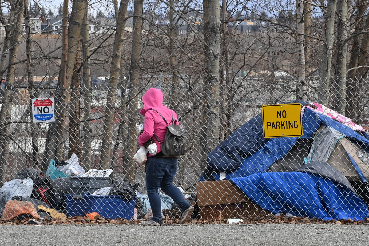 A person enters a homeless camp located on the bluff overlooking the Ship Creek area off Eagle Street on Wednesday, May 5, 2021. (Bill Roth / ADN)