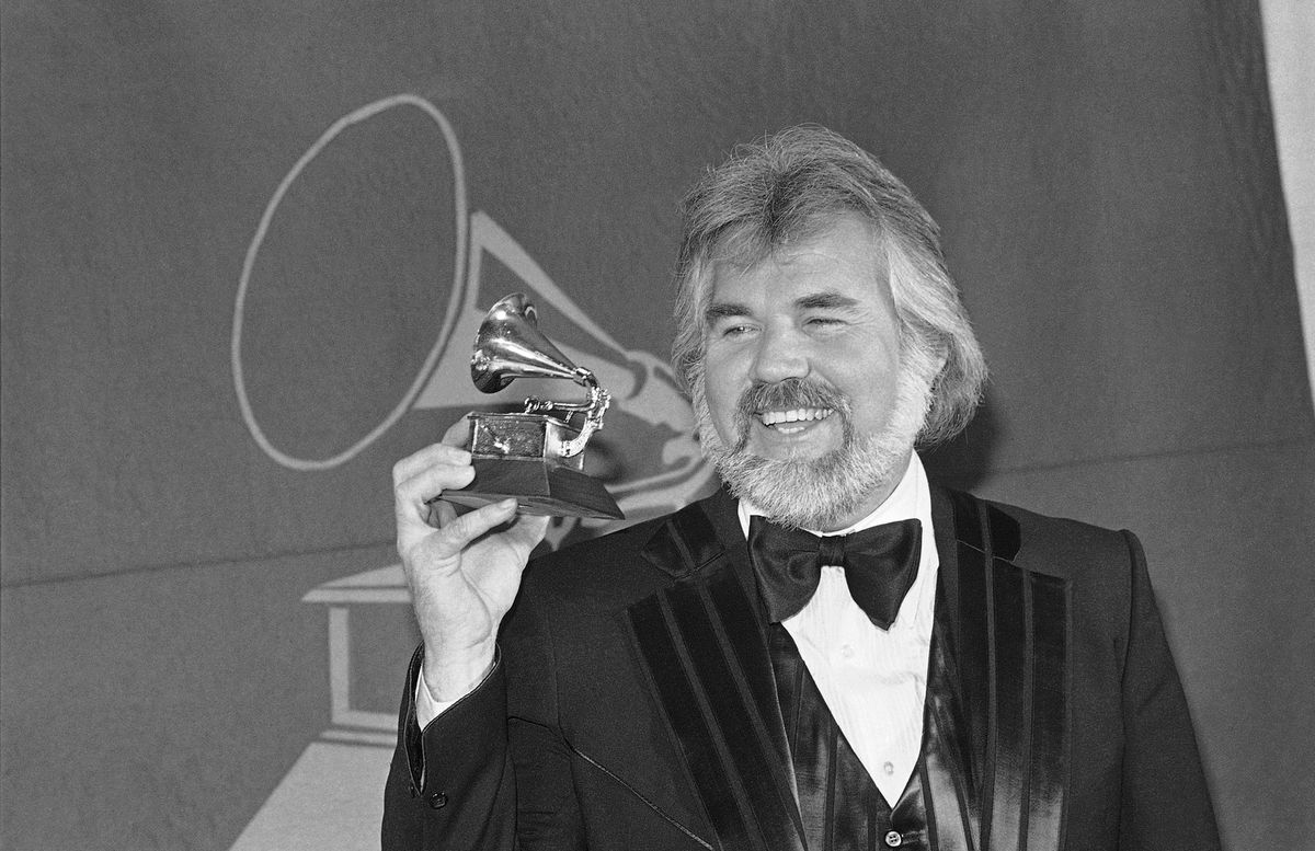 """FILE- In this Feb. 28, 1980 file photo, Kenny Rogers holds a Grammy Award he received during presentation in Los Angles. Rogers, who embodied """"The Gambler"""" persona and whose musical career spanned jazz, folk, country and pop, has died at 81. A representative says Rogers died at home in Georgia on Friday, March 20, 2020. (AP Photo/McLendon, File)"""