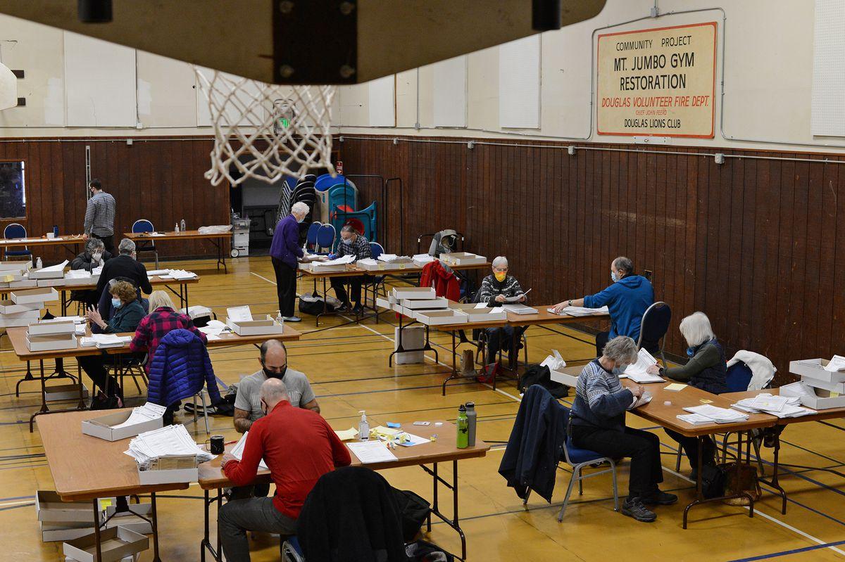 Basketball nets hang above election workers at Mount Jumbo Gym on Wednesday, Nov. 18, 2020 in Juneau, Alaska. (James Brooks / ADN)