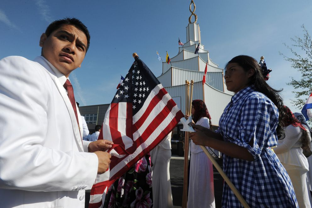 Joab Cano, of Juneau, and Dana Acevedo unfurl an American flag before the inauguration ceremony for La Luz del Mundo on Thursday. (Bill Roth / ADN)