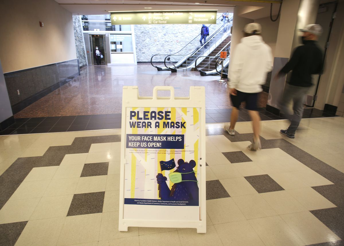 People walk past a sign requiring masks in the Ted Stevens Anchorage International Airport on July 17, 2020. (Emily Mesner / ADN)