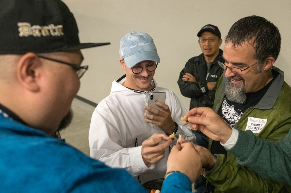 Portugal. The Man singer John Gourley instagrams a bite of muktuk that he ate before the show Friday, Oct. 26, 2018 at the Alaska Airlines Center. Shishmaref resident Dennis Davis, left, brought the muktuk, as well as dried caribou and dried fish. Bethel-raised writer Don Rearden, right, partakes as well. (Loren Holmes / ADN)