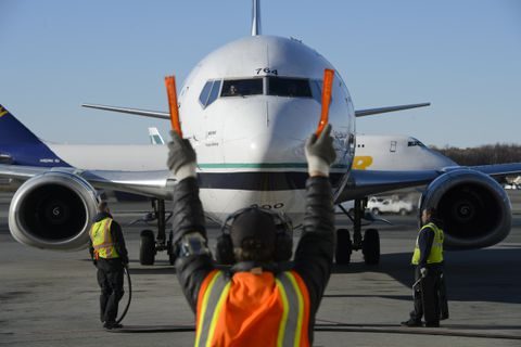 Ramp service agent Shane Spearman, center, guides an Alaska Airlines 737-400 Combi plane toward a gate at Ted Stevens Anchorage International Airport. The final flight of an Alaska Airlines Boeing 737-400 Combi aircraft departed Anchorage on Oct. 18, 2017. Alaska Airlines operated five of the jets, which were configured to carry freight in the front and passengers in the rear. The company is transitioning to dedicated cargo aircraft in Alaska. (Marc Lester / Alaska Dispatch News)