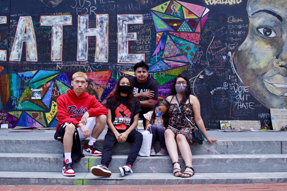 Johnny Leyua, left, and Stephanie Leyua, center, visited Portland from Salt Lake City with their family Friday and said the image of the city put forth by federal officials and right-wing media did not comport to what they saw touring downtown. (Eder Campuzano | The Oregonian)