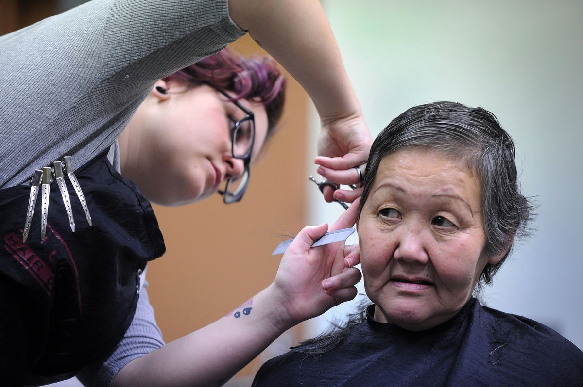 Mykala Bailey, from Studio FX, cuts Susanna Osness' hair during Project Homeless Connect at the Egan Center in downtown Anchorage on Wednesday. (Bob Hallinen / Alaska Dispatch News)