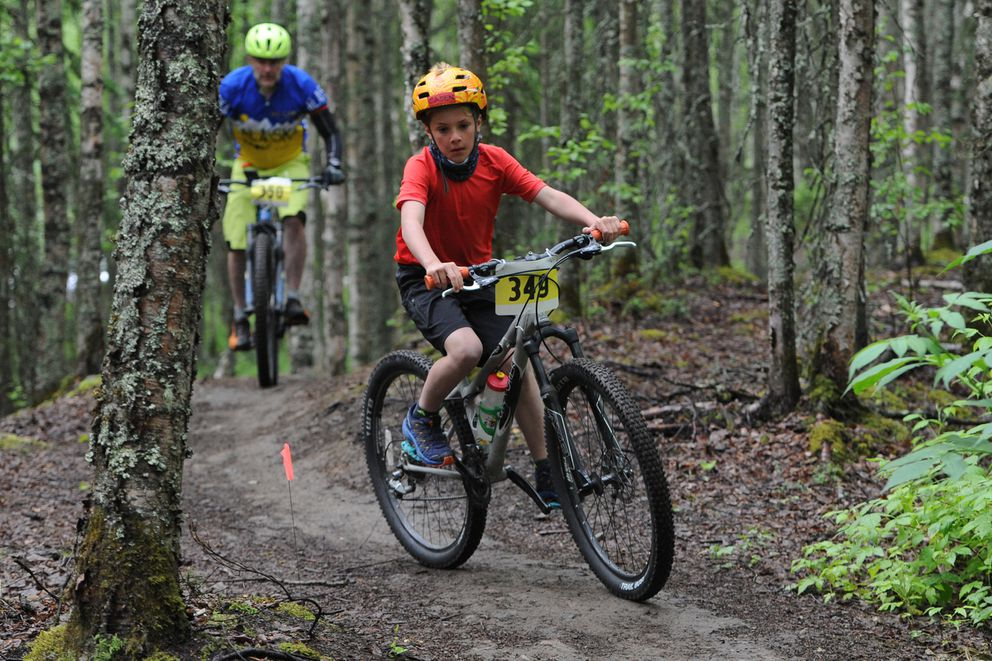 Caden and Mike Grunst ride together on the single track trails. (Bill Roth / ADN)