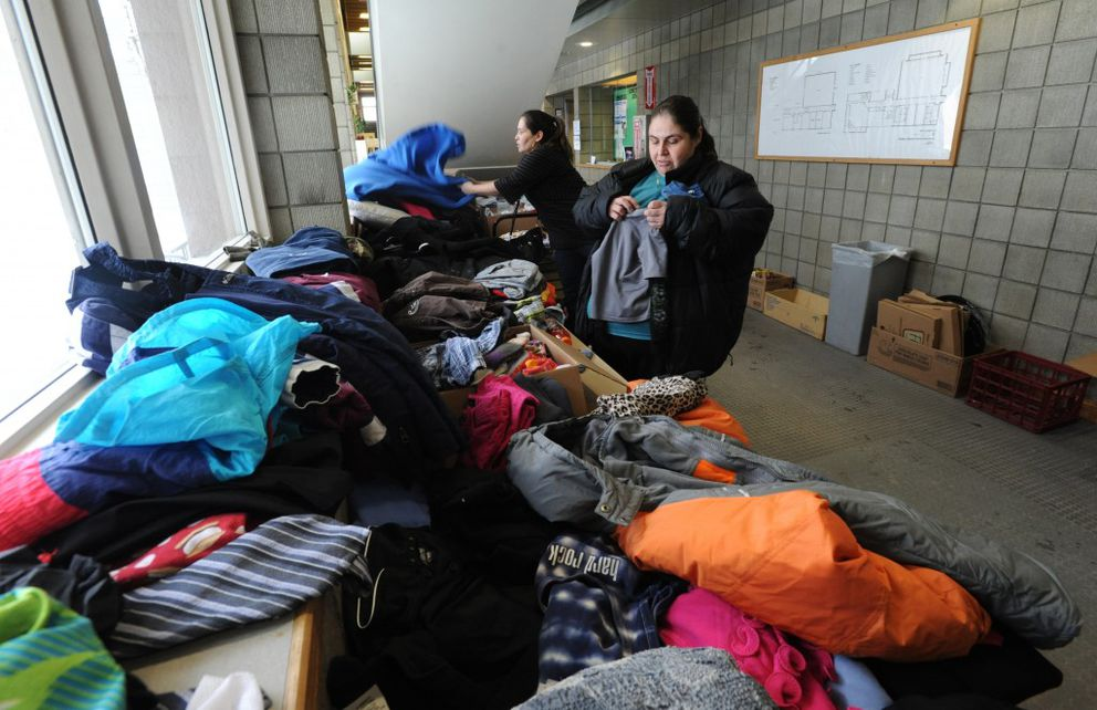 Carmen Eakon, left, and Angela Grice help pick out clothes for Eakon's sister Dawn Eakon and her five children at the American Red Cross shelter set up in the Spenard Recreation Center on Thursday, Feb. 16, 2017. Dawn Eakon was a resident on the third floor Royal Suite Apartments. (Bill Roth / Alaska Dispatch News)