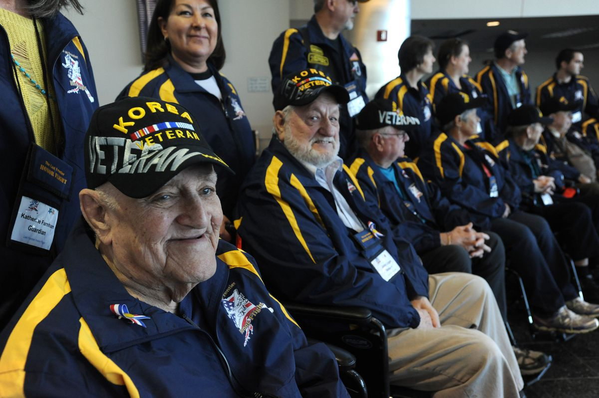 Bob Roland, left, who served in the U.S. Navy during the Korean War as a gunner on a gasoline tanker delivering fuel to shallow ports along the coast, smiles during a Last Frontier Honor Flight group photo on Tuesday. (Bill Roth / ADN)