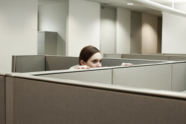 Woman hiding behind cubicle in office (Getty)