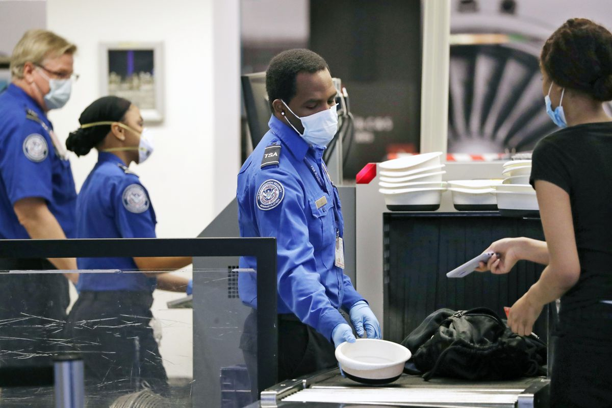 TSA officers wear protective masks at a security screening area at Seattle-Tacoma International Airport Monday, May 18, 2020, in SeaTac, Wash. Airlines say they are stepping up security on flights to Washington before next week's inauguration of President-elect Joe Biden. Delta, United and Alaska airlines said Thursday, Jan. 14, 2021 they will bar passengers flying to Washington from putting guns in checked bags. (Elaine Thompson / Associated Press archive 2020)